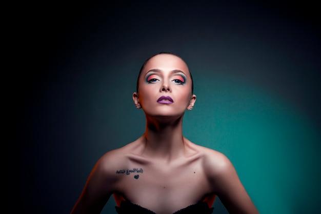 Maquillaje de arte de belleza en la cara de una chica mujer con pelo rojo. chica perfecta con grandes ojos azules sobre un fondo verde. cosmética profesional para el cuidado de la piel del rostro y el cuerpo.
