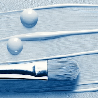 Maquillaje base líquida, corrector y pincel cosmético, tonos azules.