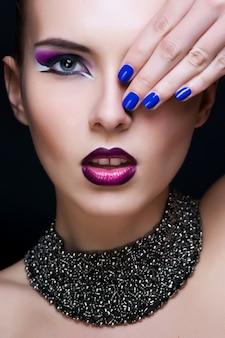 Maquillaje de belleza. maquillaje morado y uñas brillantes de colores