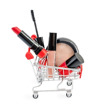 Maquillaje en la carretilla de mano aislada en el fondo blanco. lápiz labial rojo, rímel, brillo labial rosa, polvo, esmalte de uñas. productos de maquillaje en carrito de compras, descuento o tema de venta. debe tener y favoritos de belleza