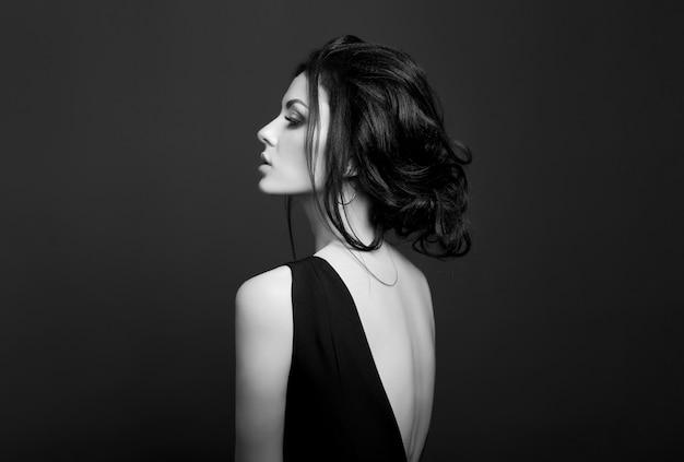 Maquillaje clásico smokey en cara de mujer, hermosos ojos grandes. moda maquillaje perfecto, ojos expresivos en el rostro de una mujer, cejas lisas y negras, cabello castaño lamido. retrato de una mujer en una pared oscura