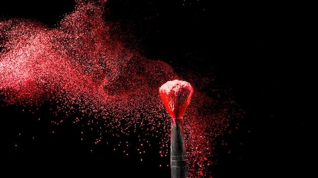Maquillaje y concepto de belleza. pincel con explosión de polvo rojo sobre negro