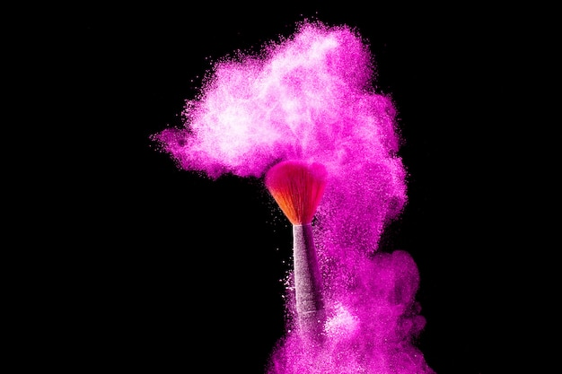 Maquillaje y concepto de belleza. pincel con explosión de polvo rosa sobre fondo negro