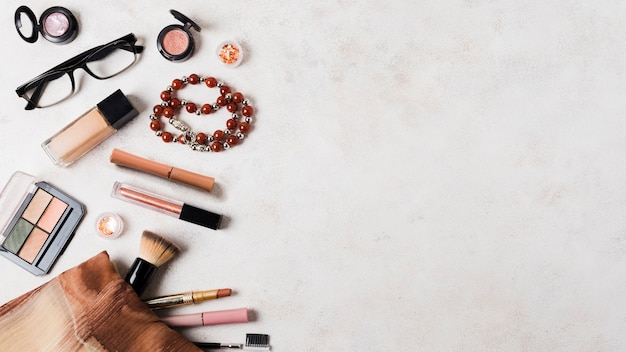 Maquillaje cosmética con accesorios en superficie clara.