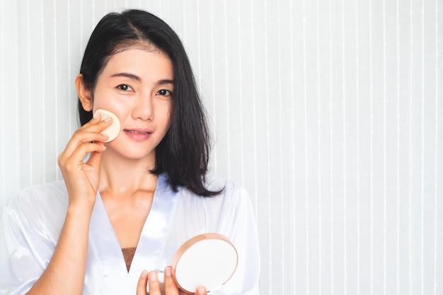 Maquillaje facial. hermosa mujer asiática aplicando polvo en la cara