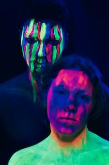 Maquillaje fluorescente en rostro de mujer y hombre