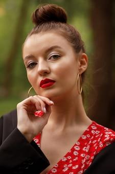 Maquillaje glamoroso de verano para la fiesta. modelo mira a la cámara. labios en lápiz labial rojo. piel bronceada