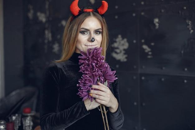 Maquillaje de halloween hermosa mujer con peinado rubio. chica modelo en traje negro. tema de halloween.