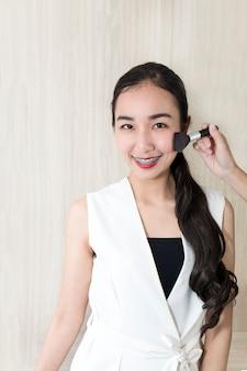 Maquillaje hermoso joven de la prueba de la mujer con la cara para enviar.