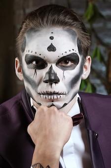 Maquillaje masculino del cráneo del azúcar. arte de la pintura de la cara.