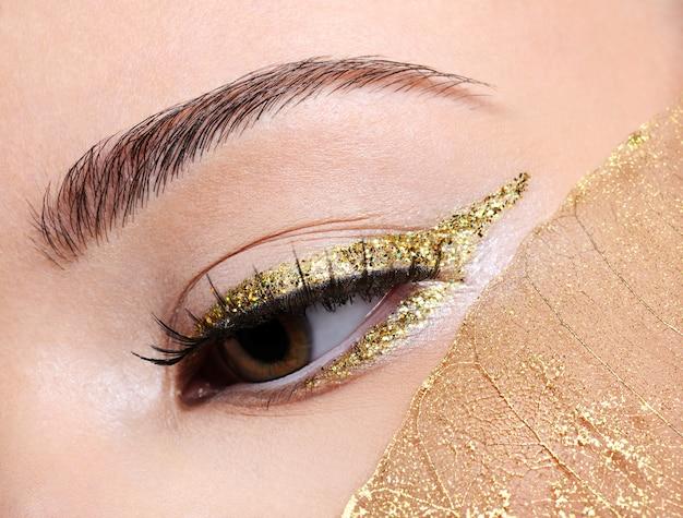 Maquillaje de moda en flecha delineador de ojos dorado en la mujer con una hoja amarilla