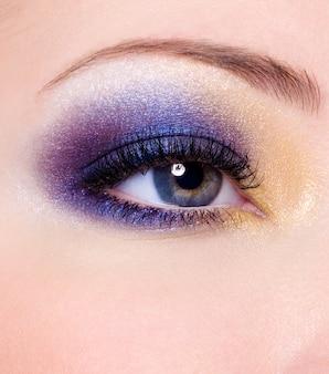 Maquillaje de moda multicolor moderno de un ojo femenino