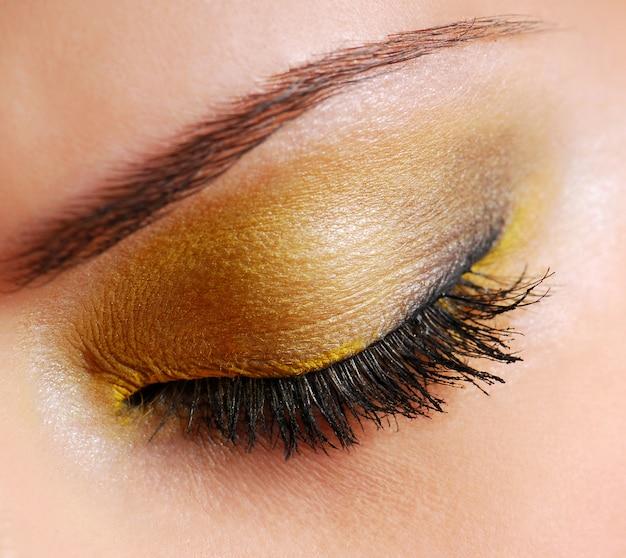 Maquillaje de moda: sombra de ojos de color amarillo brillante en los ojos cerrados