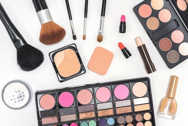 Maquillaje paleta de cosméticos y pinceles sobre fondo blanco