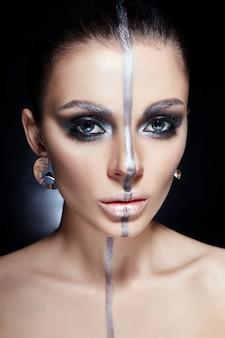 Maquillaje perfecto de moda, banda de color plateado en la cara de niña, cejas plateadas