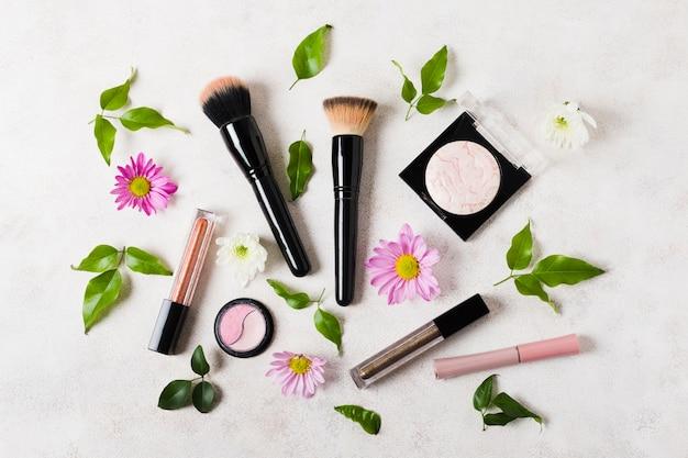 Maquillaje pinceles y cosméticos con margaritas.