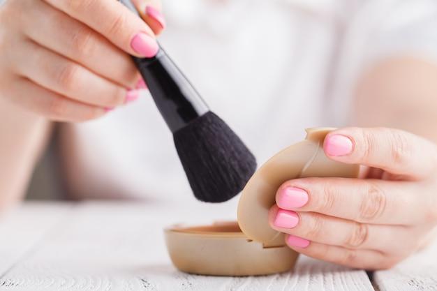 Maquillaje en polvo y brocha en mano