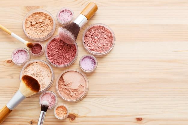 Maquillaje en polvo y pinceles sobre fondo de madera