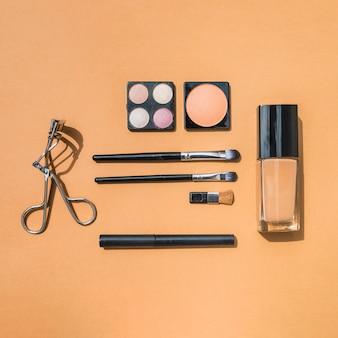 Maquillaje y productos de belleza cosméticos sobre fondo ocre