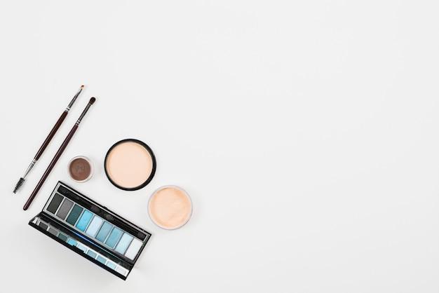 Maquillaje y productos de belleza en la paleta azul sobre fondo blanco
