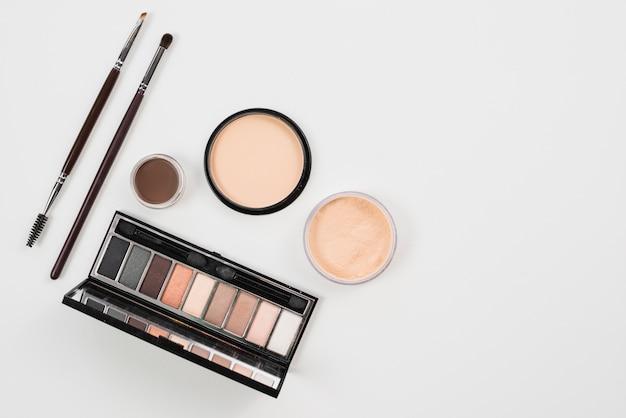 Maquillaje y productos de belleza en paleta natural.