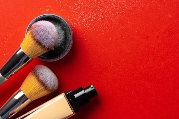 Maquillaje productos y cosméticos sobre fondo rojo. de cerca.