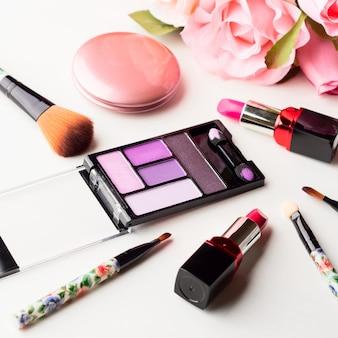 Maquillaje productos y herramientas con rosas rosadas.