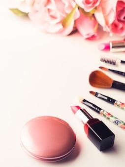 Maquillaje productos y herramientas con rosas rosas en blanco.