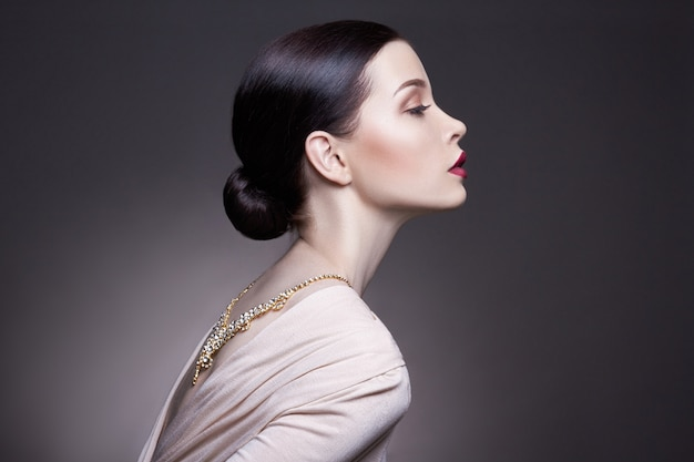 Maquillaje profesional de la mujer morena joven del retrato