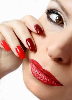 Maquillaje rojo y manicura en uñas largas.
