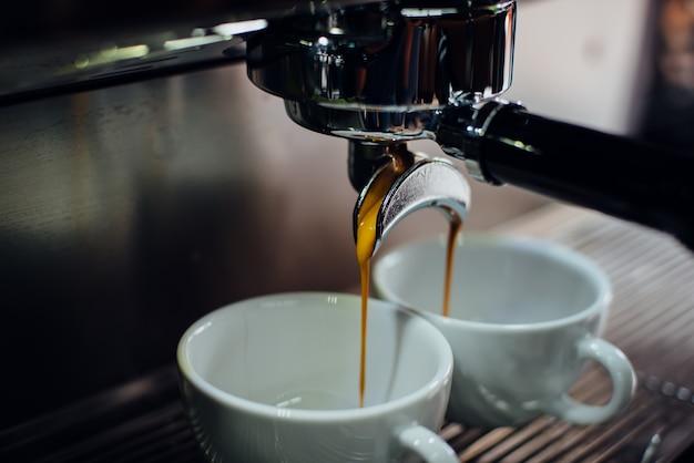 Máquina de café llenando dos tazas a la vez
