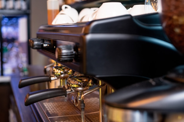 Máquina de café moderna con dos asas de plástico negro, interruptores sobre ellos y pila de tazas de porcelana blanca para capuchino
