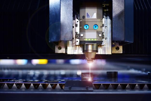 Máquina de corte láser industrial mientras se corta la chapa con la luz de encendido.