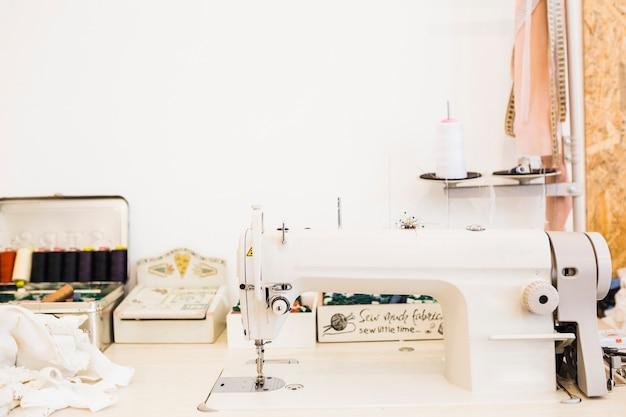 Máquina de coser y equipos de tela en el banco de trabajo