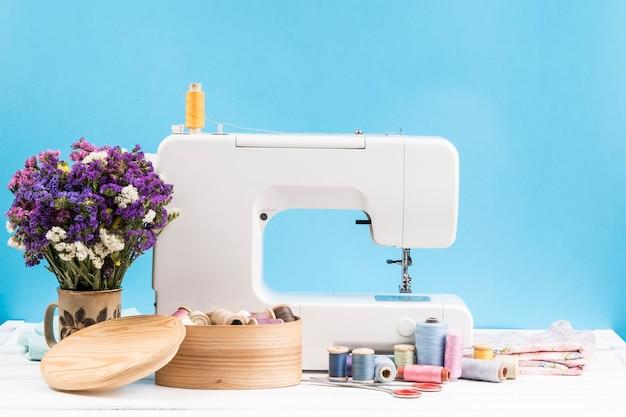 Máquina de coser con flores sobre fondo azul.