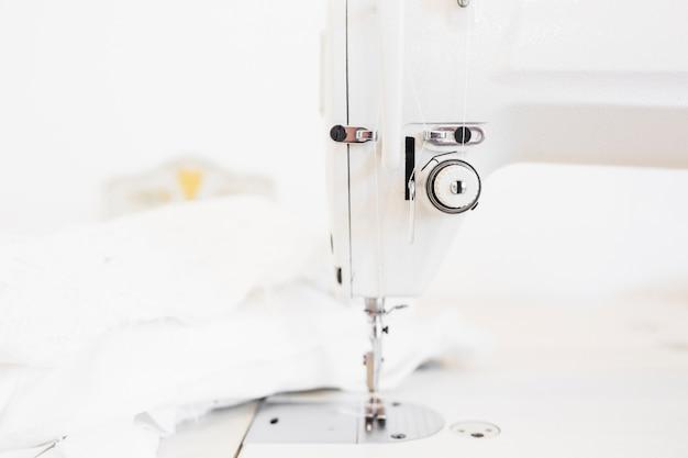 Máquina de coser y tela en el escritorio de trabajo de diseño