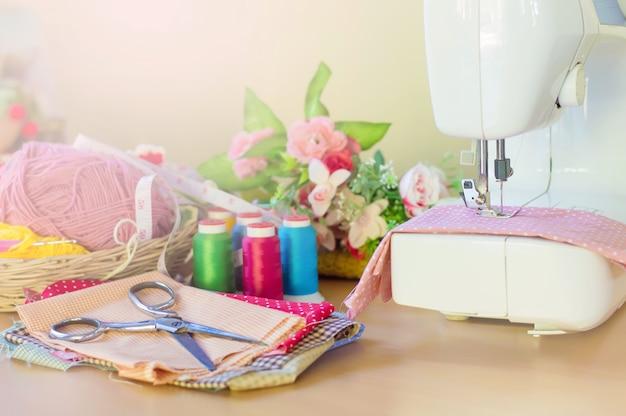 Máquina de coser sobre la mesa con accesorios para coser