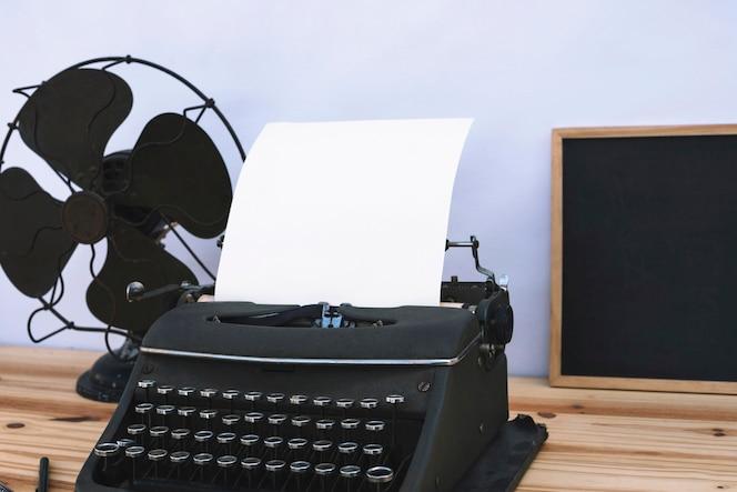 Máquina de escribir entre pizarra y ventilador