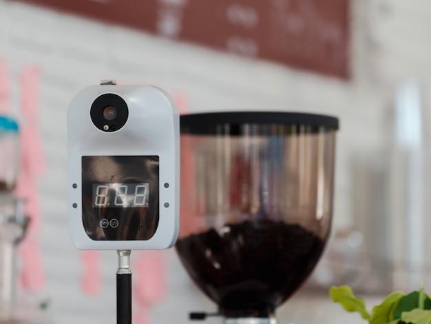 Máquina digital de enfoque selectivo de primer plano para medir la temperatura corporal colocando la mano o la frente sobre el sensor en la cafetería para controles obligatorios de los clientes durante la pandemia de covid-19