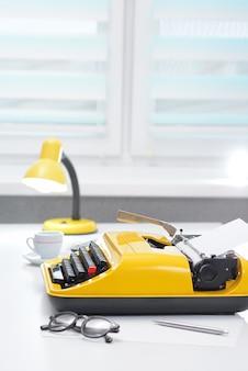 Máquina de escribir amarilla con lámpara y café en el escritorio de oficina blanco cerca de la ventana