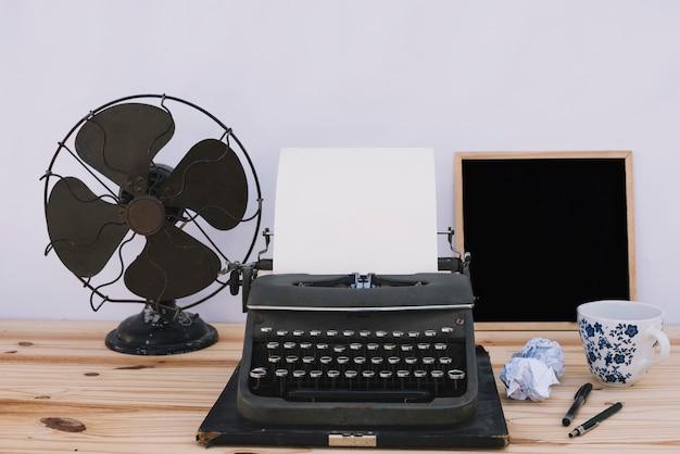 Máquina de escribir cerca de pizarra y ventilador