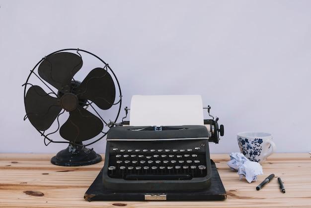 Máquina de escribir cerca de ventilador y taza