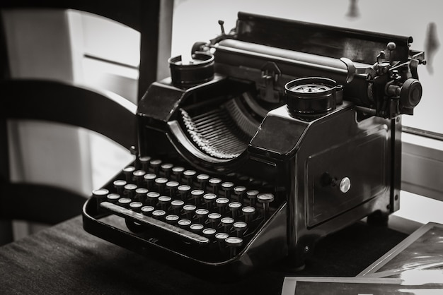 Máquina de escribir manual antigua sobre la mesa del escritor, frente a la ventana