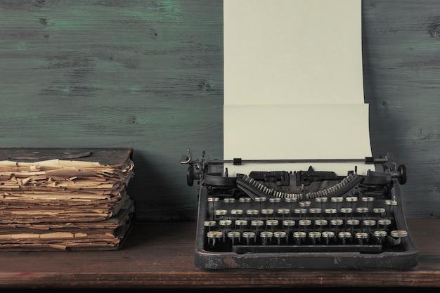 Máquina de escribir con papel y libros antiguos
