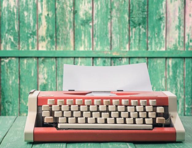 Máquina de escribir roja en una pared rústica verde