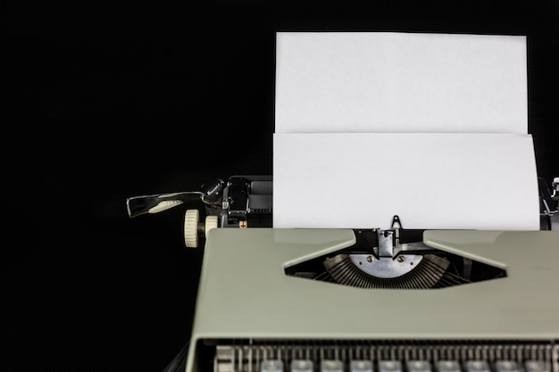 Máquina de escribir sobre la mesa en una pared negra con papel blanco con espacio vacío. lugar de trabajo del escritor o autor. nuevo concepto de vida.