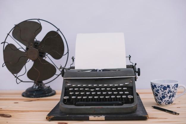 Máquina de escribir entre taza y ventilador