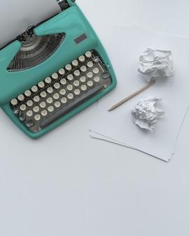 Una máquina de escribir vintage azul con hojas de papel, plantilla y bolas de papel sobre fondo blanco.