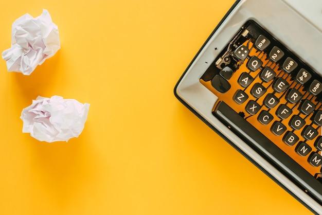 Máquina de escribir vintage con bolas de papel desechadas sobre un fondo amarillo esperando que escribas tu mejor novela.