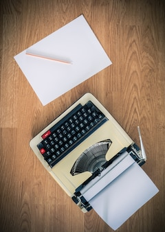 Máquina de escribir vintage y una hoja de papel en blanco